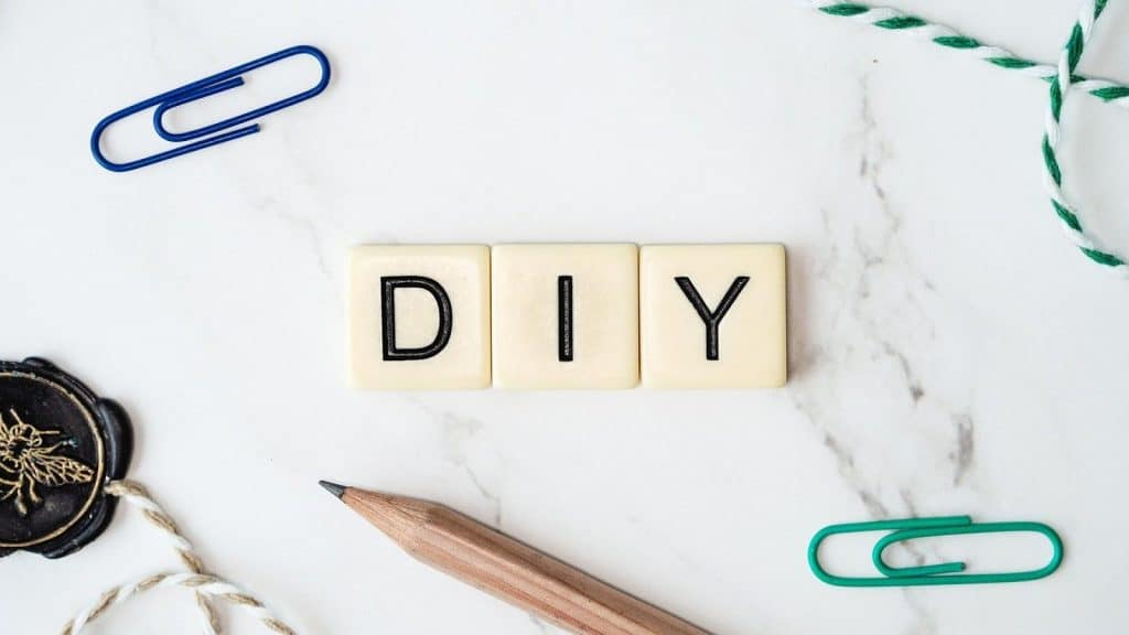 Scrabble board pieces spelling out 'DIY' on a white marble top
