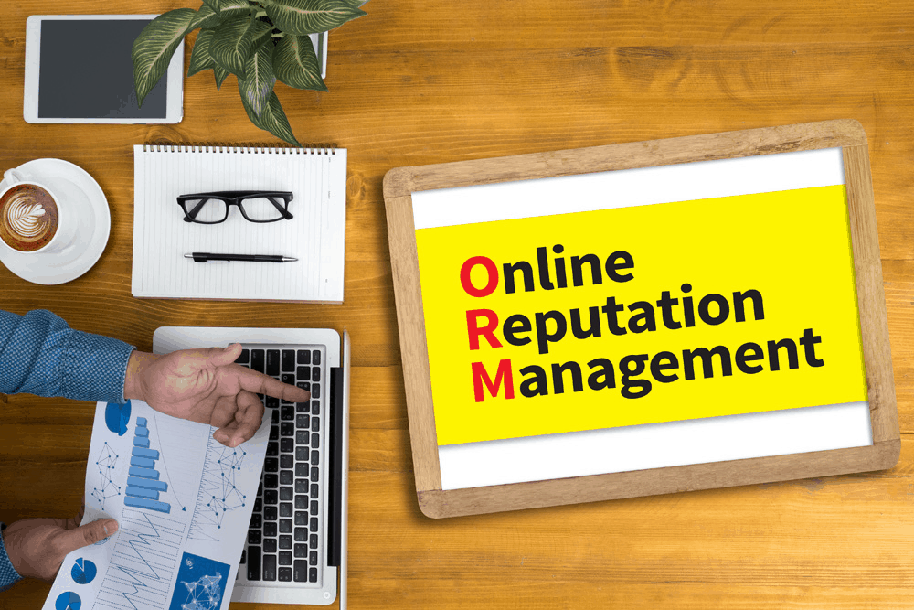 Yellow sheet on a wooden table saying 'Online Reputation Management' listed below one another with the first letter of each word in red. Glasses and a pen on a white notepad with a coffee and someone's hands visible on a latop keyboard